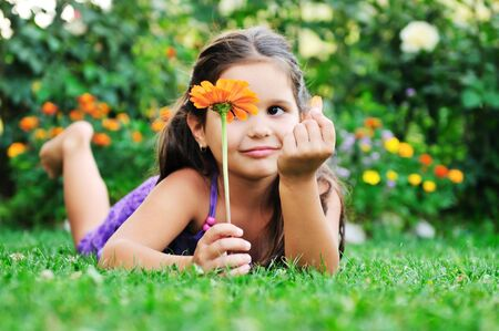 happy young girl children relax lie and have fun on grass with flower photo