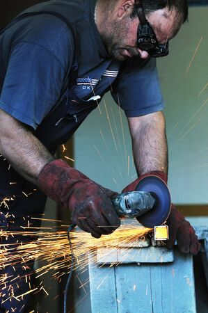 manual job: industry worker cut steel with spinning machine and spark Stock Photo