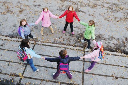 amistad: Ni�o feliz grupo permanente al aire libre juntos en formaci�n de c�rculo y que representa el concepto de trabajo en equipo y la amistad