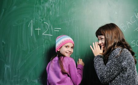 happy child in school classrom solving math problem and have friend to help find solution  photo