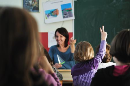 girls back to back: happy young teacher woman at elementrary school teaching and giving leassons to group of young smart children Stock Photo