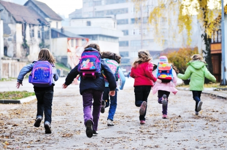 primary colours: happy school girls running outdoor at sunny autumn day  Stock Photo