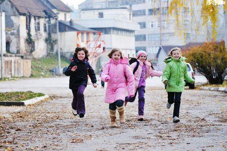 happy school girls running outdoor at sunny autumn day  photo