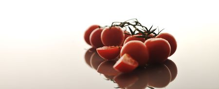 small wet fresh red tomato group isolated on white with glossy surface reflection photo