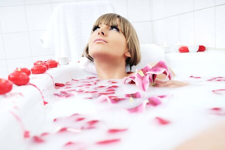 young girl bath: woman beauty spa and wellness treathment with red flower petals in bath with milk  Stock Photo