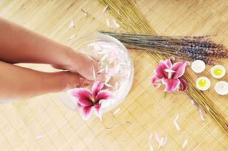 woman spa pedicure foot treatment with water and flower photo