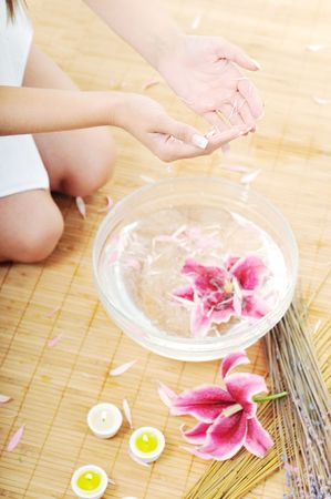 hand  and nail spa and beauty treatment with aroma and flowers in water isolated on white photo