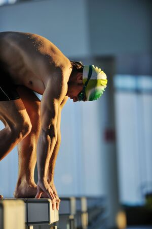commence: start position race concept with fit swimmer on swimming pool Stock Photo