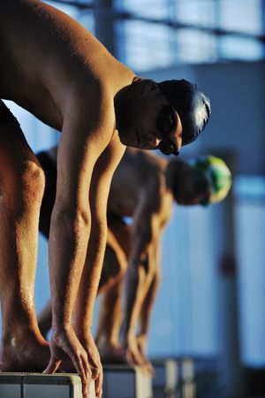 start position race concept with fit swimmer on swimming pool  photo