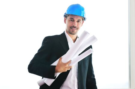 appartment: happy young architect portrait with helmet and blueprints indoor at new big bright appartment and construction site Stock Photo