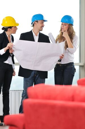 young arhitect group in big bright modern new apartment looking blueprints and building plans Stock Photo - 6141751