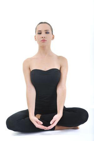 young brunette woman in black sport wear meditating yoga in lotus postition isolated on white background photo