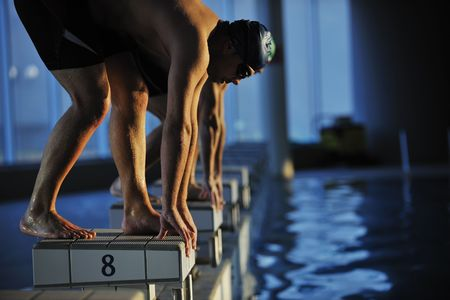 swimming competition: start position race concept with fit swimmer on swimming pool Stock Photo