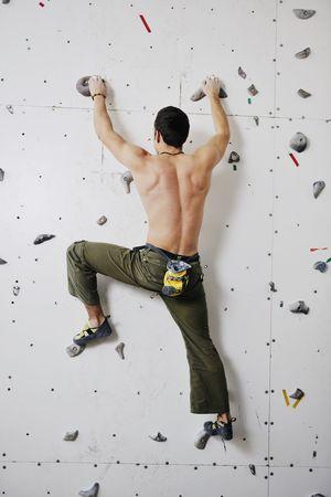 escalando: hombre joven y ajustar ejercer monta�ismo libre en la pared interior de la pr�ctica