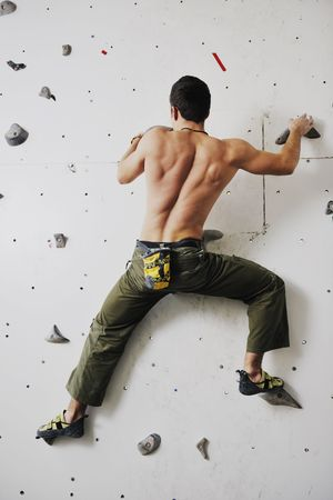 climbing sport: young and fit man exercise free mountain climbing on indoor practice wall