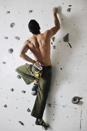 young and fit man exercise free mountain climbing on indoor practice wall Stock Photo - 6274143