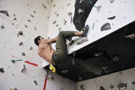 young and fit man exercise free mountain climbing on indoor practice wall Stock Photo - 6322124
