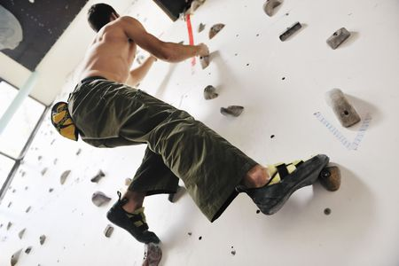 climbing wall: young and fit man exercise free mountain climbing on indoor practice wall