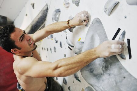 young and fit man exercise free mountain climbing on indoor practice wall photo