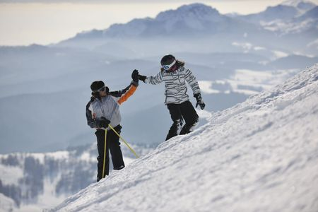 snow ski: happy couple drivingand relaxing with snowboard and ski at winter seasson on mountain