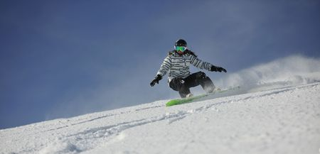 snowboarder jumping: snowboard woman racing downhill slope and freeride on powder snow at winter season and sunny day