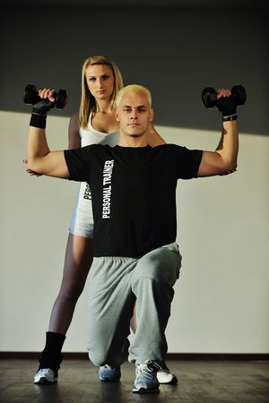 fitness personal trainer in fitness club exercise with client photo