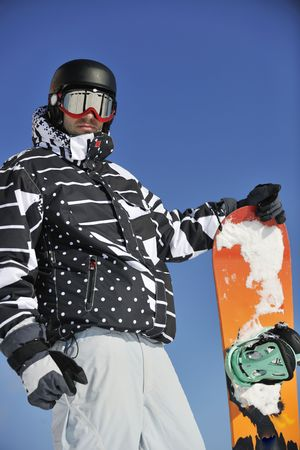 travel gear: snowboarder relaxing and posing at sunny day on winter season with blue sky in background
