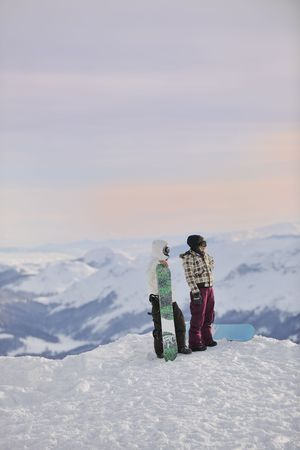 happy young snowboarder couple relax at top of mountain at\ beautiful sunny winter day