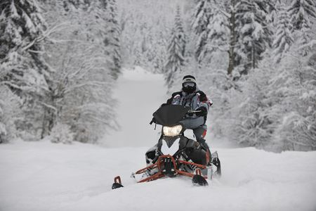 outside machines: young man posing on snowmobile at beautiful winter day