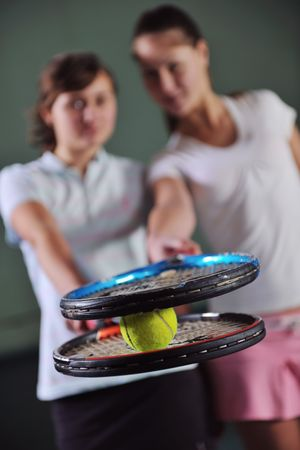 young girls playing tennis game indoori in tennis court photo