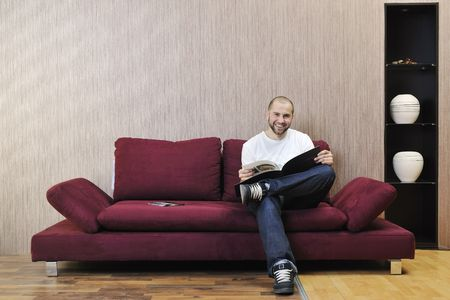 livingroom: happy smling young man reading newspaper and relaxing in modern living room with fancy furniture and sofa