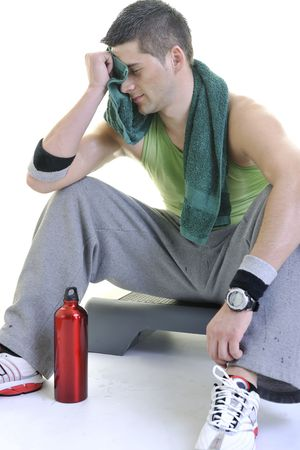 sweating: young adult man relax and drink water with sweat on body Stock Photo
