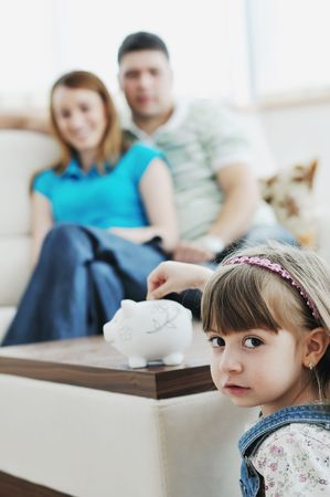 young parrent at home with beautiful child make savings and put coins money in piggy bank Stock Photo - 6742338