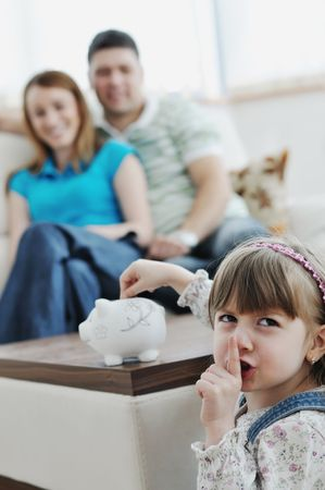 young parrent at home with beautiful child make savings and put coins money in piggy bank Stock Photo - 6742337