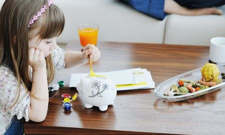 young parrent at home with beautiful child make savings and put coins money in piggy bank Stock Photo - 6742354