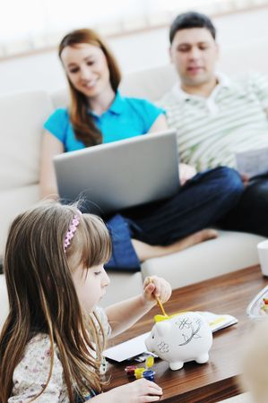 young happy family at bright and modern living room puting money in piggy bank and working on laptop computer on home finance Stock Photo - 6742333