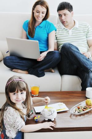 young happy family at bright and modern living room puting money in piggy bank and working on laptop computer on home finance Stock Photo - 6742329