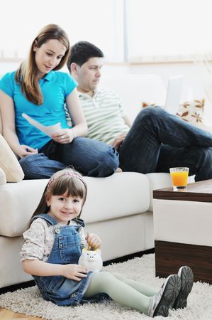 young happy family at bright and modern living room puting money in piggy bank and working on laptop computer on home finance photo
