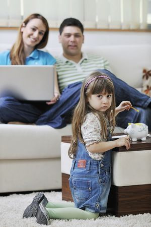 young happy family at bright and modern living room puting money in piggy bank and working on laptop computer on home finance Stock Photo - 6742402