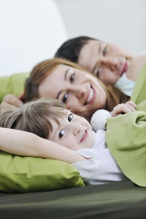 happy young family relaxing in bed  photo
