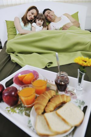 happy young family eat breakfast in bed at morning  photo