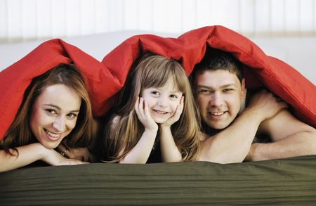 happy young family relaxing in bed Stock Photo - 6751701