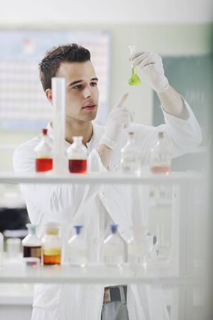biomedical research: young man scientist in chemistry bright lab