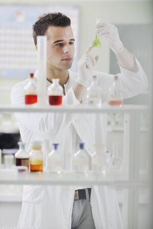 young man scientist in chemistry bright lab photo
