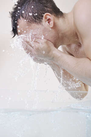 washing face: young man washing face with clean water and representing hygiene and mans beauty concept