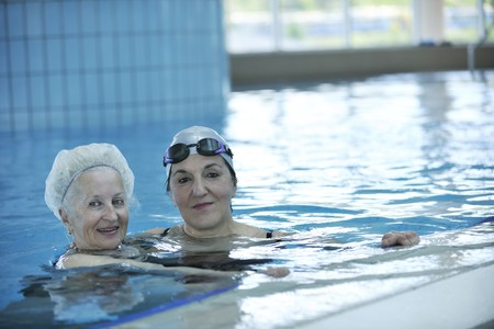 pensioner: beautiful old senior  woman have fun and recreation on swimming pool