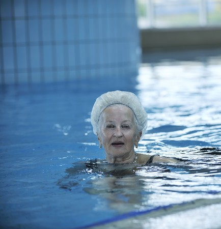 a year older: beautiful old senior  woman have fun and recreation on swimming pool