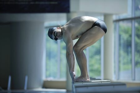 young swimmer on swim start at swimming pool ready for jump race and win photo