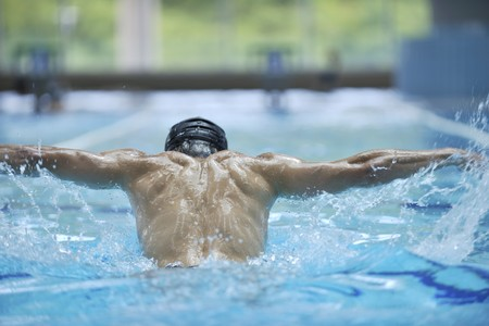 swimming goggles: young healthy with muscular body man swim on swimming pool and representing healthy and recreation concept Stock Photo