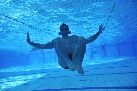 undervater shoot of swimming pool with good looking young swimmer  photo